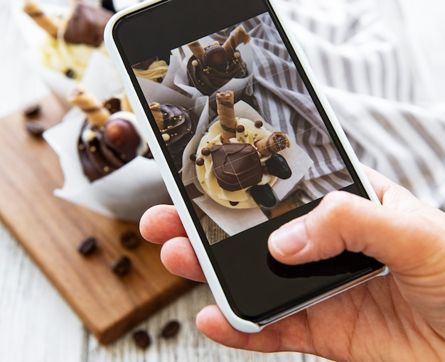 人はスマートフォンでカップケーキの写真を作ります