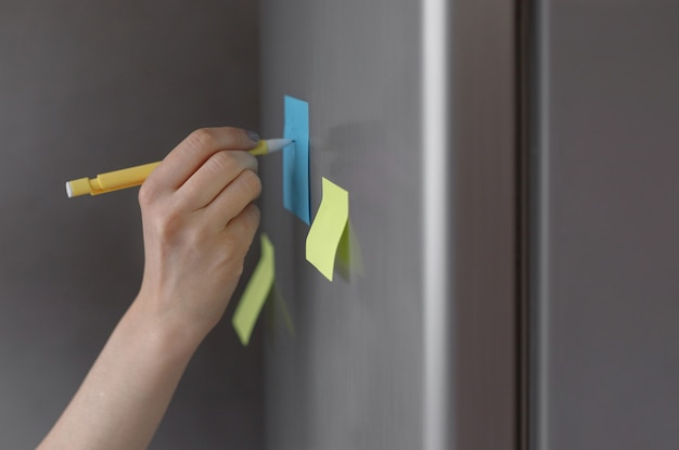 A person makes notes on a sticker on a refrigerator a reminder from a phone