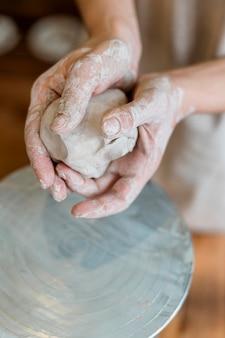 Человек, делающий глиняный горшок в своей мастерской