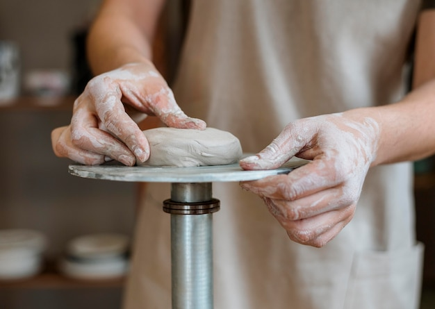 Person making a clay pot in her workshop