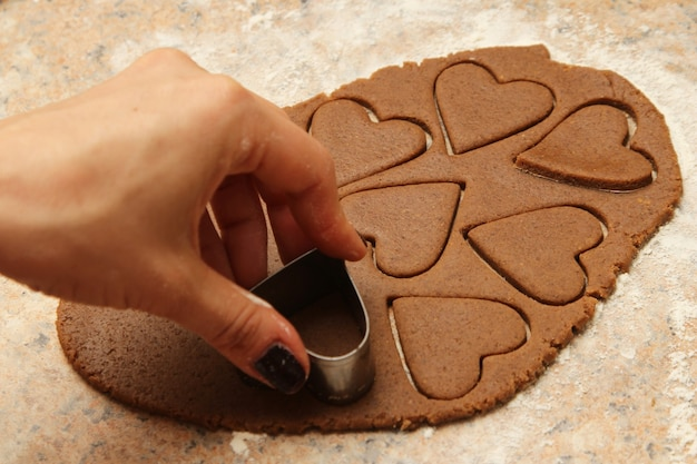 Person making delicious heart-shaped cookies