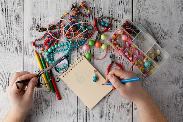 Person making earings from colorful beads and needles