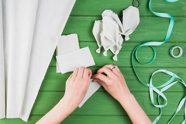 녹색 질감 된 배경 위에 크레페 종이에서 가짜 꽃잎을 만드는 사람