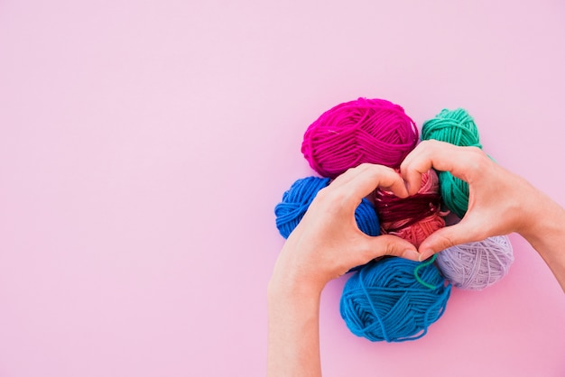 A person making heart over the colorful wool balls on pink background