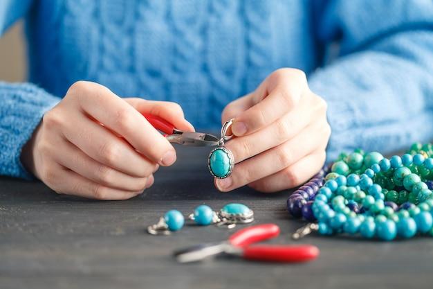 공예 도구로 와이어, 체인 및 비드 및 기타 재료를 사용하여 보석을 만드는 사람