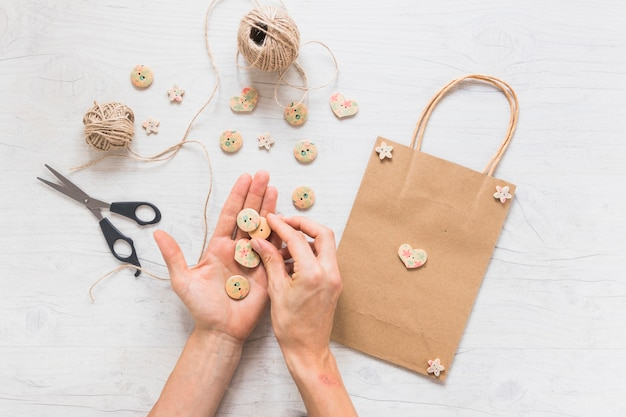 A person making shopping bag decorated with wooden button