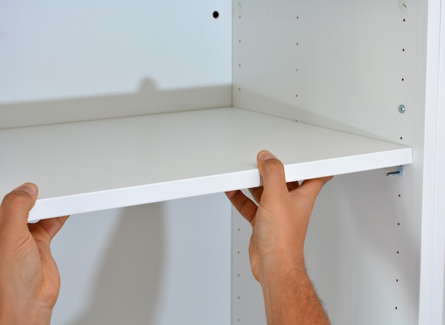 Person making a white wooden wardrobe with screws