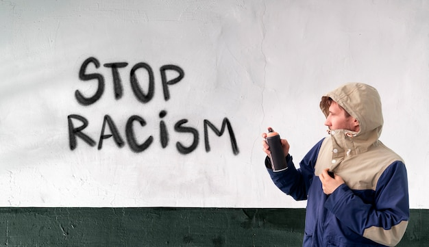 A person male write with spray paint can the stop no racism statement on the wall, graffiti symbol concept