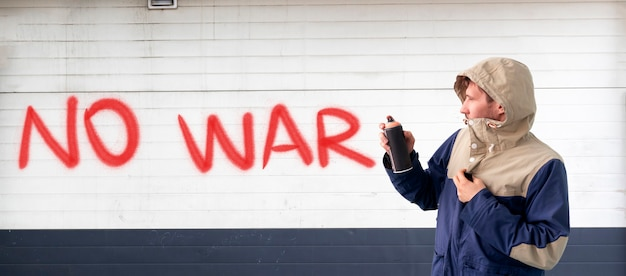 A person male write with spray paint can the stop war statement on the wall, graffiti symbol concept