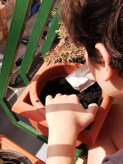 꽃을 심기 위해 냄비에 흙을 조작하는 사람