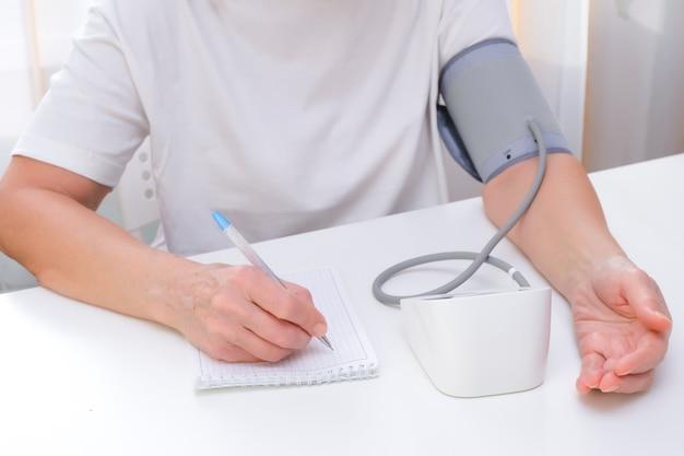 人は血圧を測定し、白い背景のノートに測定値を書き留めます。手と眼圧計がクローズアップ。