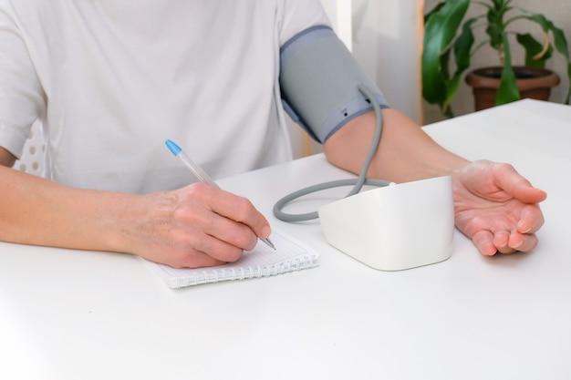 Человек измеряет артериальное давление и записывает показания в блокнот.