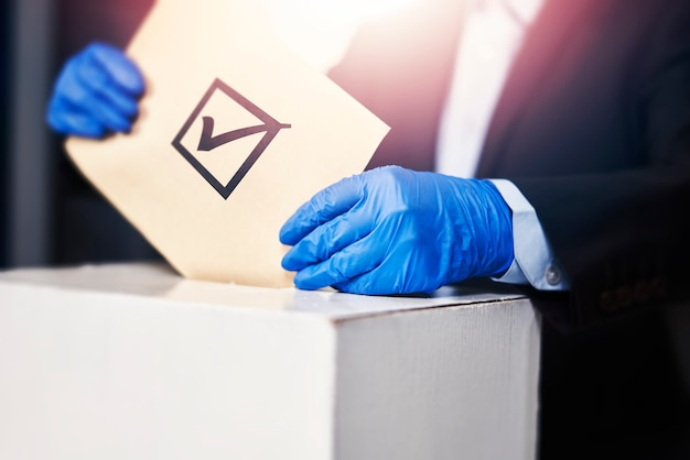 A person in medical gloves voting election concept presidential or parliament election a voter putti...