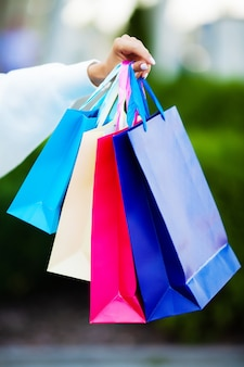 Person near shopping mall holding gift bags and calling