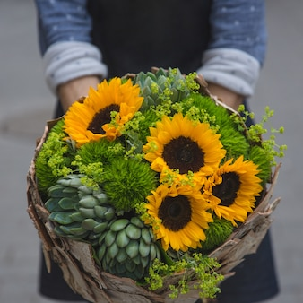A person offering a rustic bouquet of sunflowers and suculents