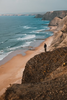 ポルトガル、アルガルヴェの美しい海を見て崖の上の人