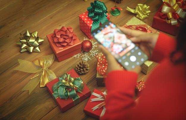 스마트폰을 사용하여 스웨터를 입은 사람이 스냅샷을 찍고 테이블에 아름다운 화려한 활과 장식품이 있는 고급스러운 선물 상자의 사진을 기록하여 크리스마스 파티의 매력적인 가정 장식을 기억합니다