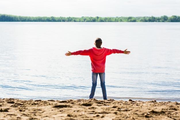 腕を伸ばして砂の中の川の土手にいる人