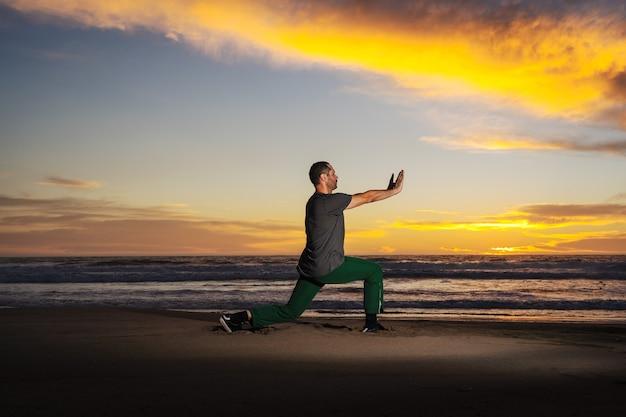 Человек на пляже занимается йогой или упражнениями на красивом закате