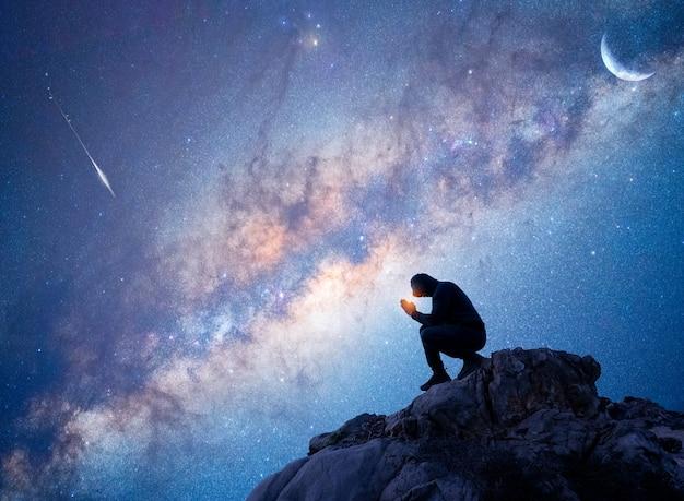 야외에서 명상을 하거나 은하수와 별똥별 아래에서 기도하는 바위 위에 있는 사람