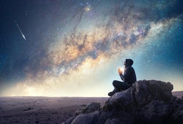 天の川と流れ星の下で夜に瞑想または祈る屋外の岩の上の人