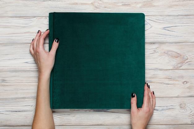 Открытая фотокнига. женщина держит семейный зеленый фотоальбом. женщины держат свадебный фотоальбом