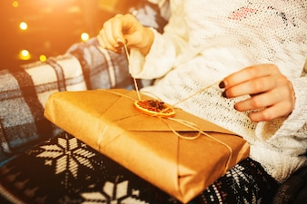 Person opening a brown gift with rope