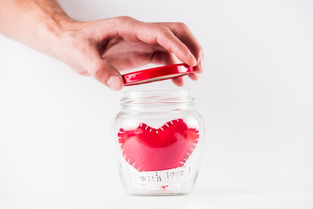 Person opening glass can withtoy heart