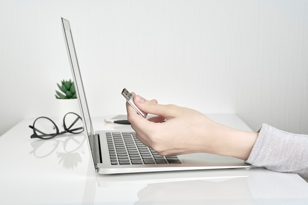 Человек, открывающий флешку рядом с ноутбуком
