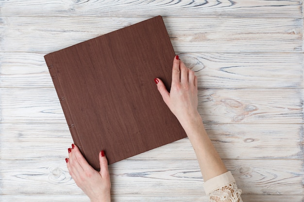 A person opens a photobook. the womans hand holding a family photo album on the table.