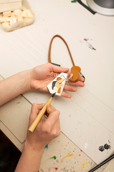 Person painting an abstract piece of wood