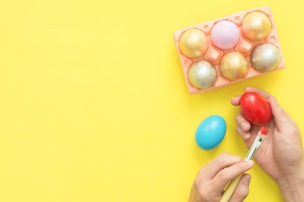 페인트 브러시로 파스텔 색상 구성으로 색칠하는 다채로운 부활절 달걀을 그리는 사람