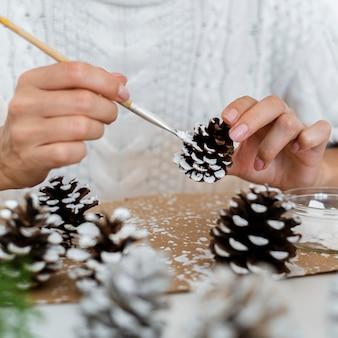 Человек рисует шишки на рождество