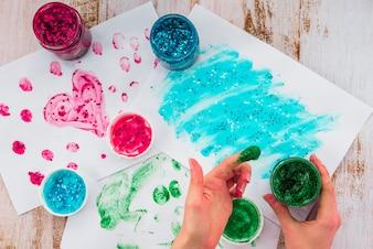 木製のテーブルの上にキラキラ色を使用して紙の上の指で絵を描く人
