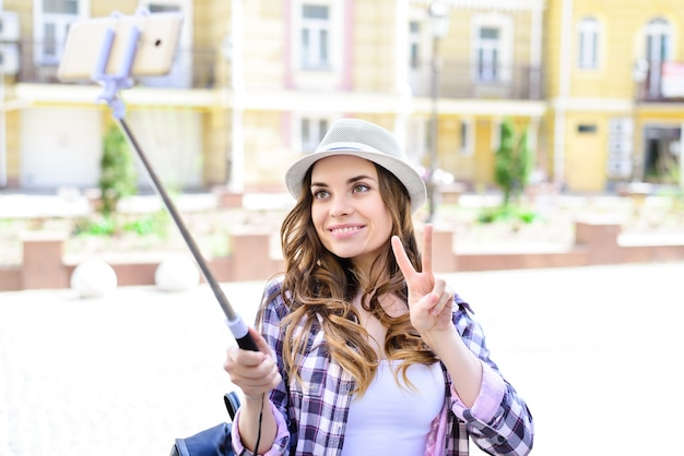 Person people hobby like want selfie mania concept. close up portrait of excited cheerful nice glad pretty beautiful sunny cute lady teenager student taking making selfie building background