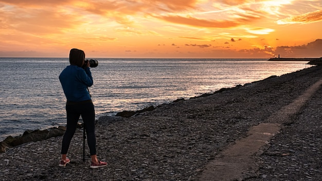 Person photographing at the sea at sunset on a summer day on the coast of portugal in aveiro