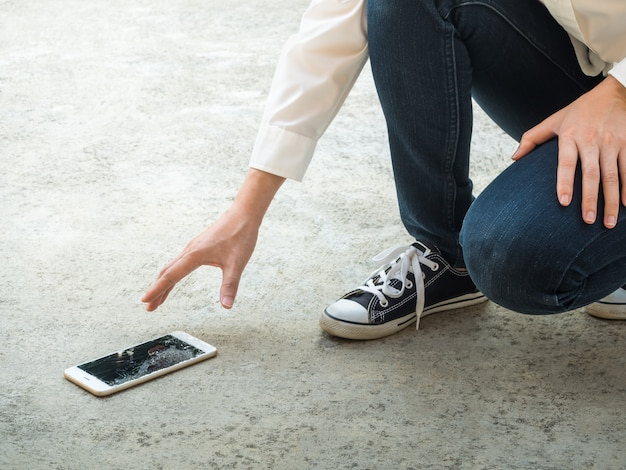 Person picking broken smart phone of ground