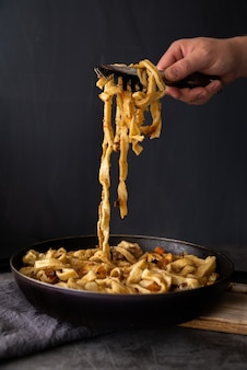Person picking up freshly cooked pasta
