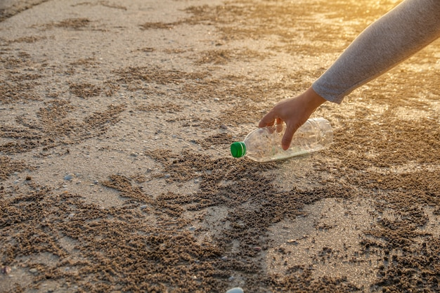 Person picking up plastic bottle cleaning on the beach