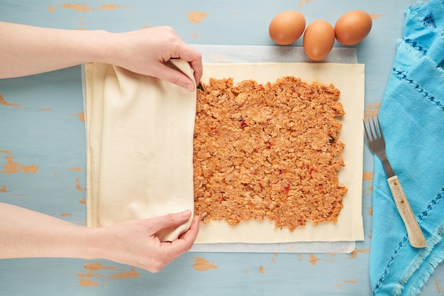 Человек кладет сырое тесто, чтобы закрыть галисийский эмпанада с тунцом.