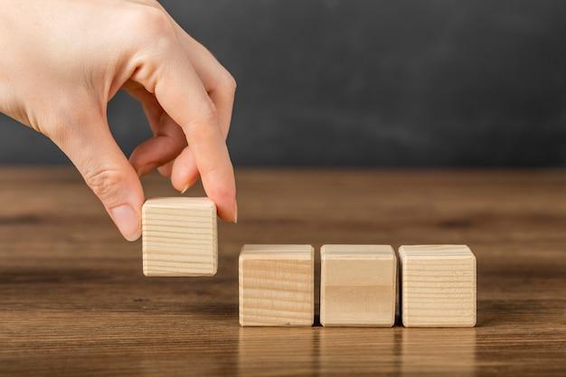 Человек кладет деревянный куб рядом с другими