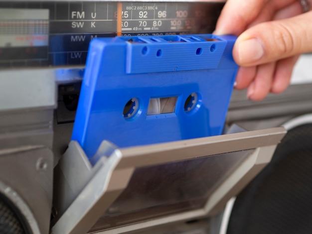음악 플레이어에 파란색 카세트 테이프를 배치하는 사람