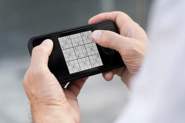 スマートフォンで数独ゲームをしている人
