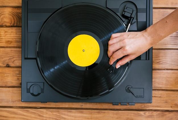 빈티지 음악 플레이어에 비닐 디스크를 재생하는 사람 무료 사진