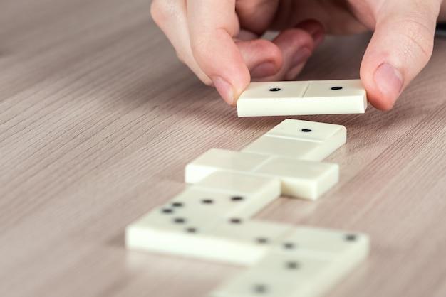 Человек, играющий в домино на деревянном столе