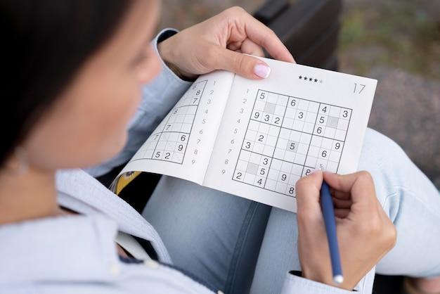 Persona che gioca da sola a un gioco di sudoku