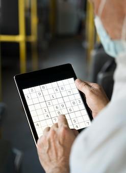 Человек, играющий в судоку на планшете