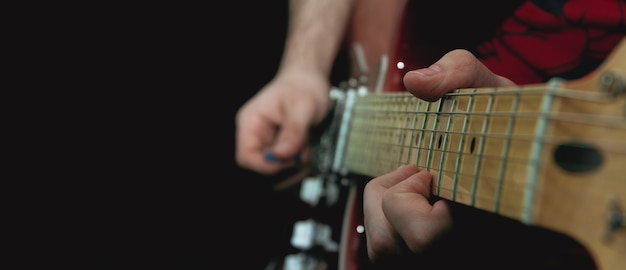 Человек щипает струны на ладах электрогитары. выборочный фокус. скопируйте пространство.