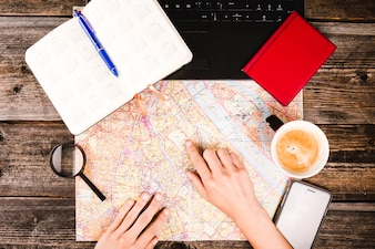 Person pointing at destination on map with cup of coffee and diary on table