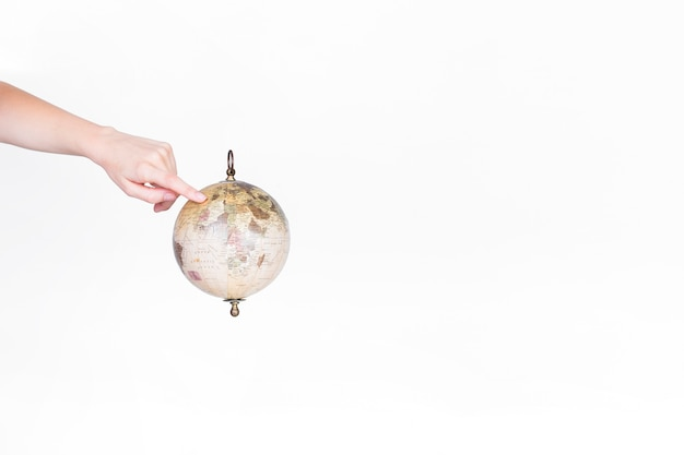 A person pointing finger at destination on globe pendulum